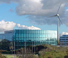 Image:  Wind turbine next to glass fronted office building