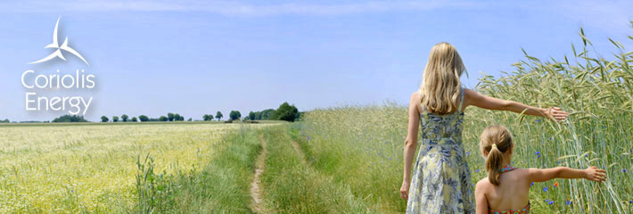 Image:  Two girls walking at the edge of a wheat field